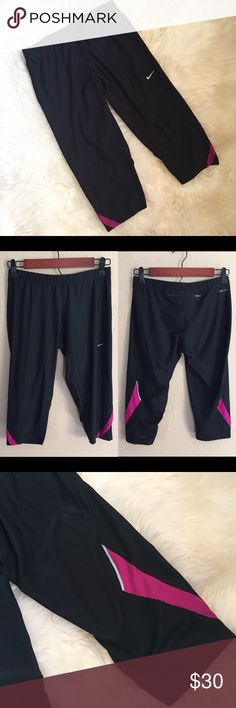 """Nike Black Dri-Fit Capri Running Pants In excellent like new condition! No tears, snags, or stains. All black with a fuchsia pink/purple color that is on the bottom pant leg on back that wraps around to the front. Also mesh panel at bottom leg at back. Dri-fit running pant with a zipper pocket at back waist. Elastic waist and drawstring on inside. Length 24""""❌NO TRADES OR PAYPAL❌ Nike Pants Capris"""
