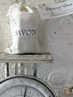 Black & white scale, with pretty bag of soap, savon. White, rusty metal tile background.