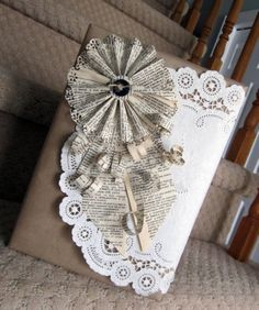 Gift wrapped in brown paper, embellished with a doily then a rosette flower & paper curls made from old dictionary pages.