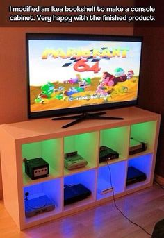 Games room, using a bookshelf to neatly store consoles/games and hide cords