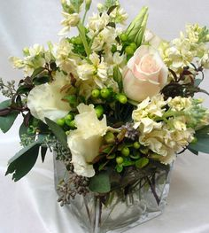 This is a cube vase floral arrangement that features roses and stock in a cream and white color scheme, with accents of green hypericum and seeded eucalyptus.  See our entire selection at www.starflor.com.  To purchase any of our floral selections, as gifts or décor, please call us at 800.520.8999 or visit our e-commerce portal at www.Starbrightnyc.com. This composition of flowers is generally available for same day delivery in New York City (NYC). SQ010