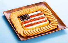 """Flatten a serving of cream cheese, then add stars and stripes with olives and salsa for this """"grand old flag"""" cheese spread."""