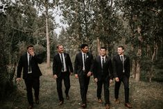 These groomsmen matched the groom with black suits + emerald green ties | Image by Erin Fraser