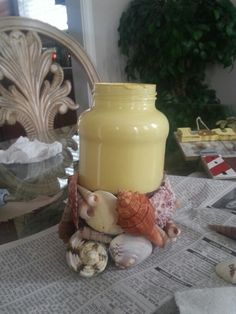 Mason jar vase painted inside. .  Burlap around bottom with seashells around .