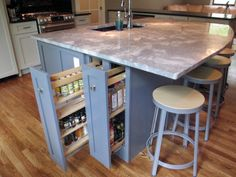 This island from ProCraft Fine Cabinet and Woodwork has two roll-out spice racks to keep everything within reach