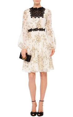 Rendered in a floral printed silk georgette, this **Giambattista Valli** dress features a high round neck with a sheer floral embroidered yoke, long balloon sleeves with cuffs at the wrists, a fitted waistband, and a fluid mini length hem.