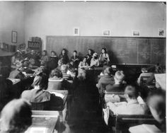 """""""Library Hour"""" at a public school in Alberta, in the 1920's. Miss Hopkins, CPL's first Children's Librarian, started the program in 1914, bringing books to schools with no budget for books, and extolling the joys of reading. This """"traveling library"""" was the first of its kind in Canada."""