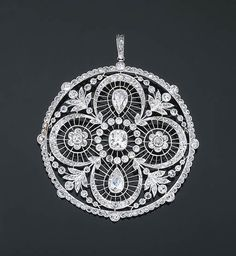 A Belle Epoque Diamond Pendant Of pierced openwork design, the central cushion-cut diamond within a diamond-set cluster, the pear-shaped drops on either side alternated with two further diamond-set clusters all within a cusp and garland surround to the old-cut diamond collet frame, circa 1890, 6.5 cm long with pendant hoop