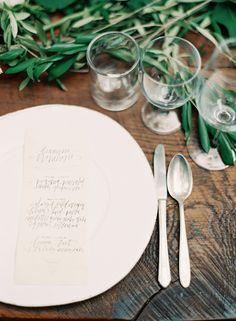 Table en bois nue, menu calligraphié au format rectangulaire posé sur l'assiette, branches d'olivier en guise de centre de table