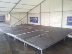 Low rise stage in tent for outdoor event, installed by www.24carrotevents.co.uk