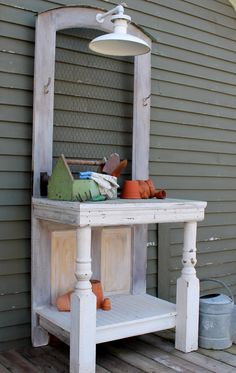 Potting bench has farmhouse light and old door w/ chicken wire
