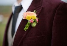 Boutonniere with peach ranunculus, yellow billy balls and poppy pod