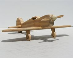 Your child can become an Ace fighter pilot with this handsome wooden toy airplane! Handmade entirely from reclaimed wood, with a rotating propeller, this toy will provide hours of fun for your child.This version has no landing gear and may be more suitable for smaller children. Looks great on a shelf as décor, or hanging from the ceiling, as shown.  dimensions: 11 inches wingspan, 11 inch length, 3 1/2 height  The actual wood fighter plane pictured has been sold, the one you receive is m...