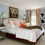 bedrooms - baby blue walls tan linen camelback headboard nailhead trim white hotel duvet shams orange monogramming stitching antique brass swing-arm sconces stacked silhouette art prints faux fur throw mirrored chests nightstands