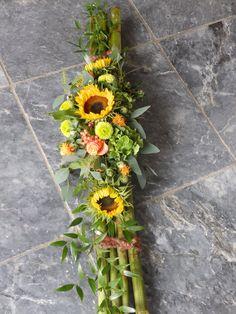 langwerpig rouwarrangement met zonnebloemen