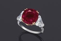 Set with a cushion-shaped ruby weighing approximately 8.99 carats, flanked by triangular-shaped diamonds, mounted in platinum and 18k yellow gold. Accompanied by report no. CS 82969 dated 24 September 2013 from the American Gemological Laboratories stating that based on available gemological information, it is the opinion of the Laboratory that the ruby weighing 8.99 carat is natural, the origin of this material would be classified as Burma (Myanmar), heat enhancement: none, clarity…