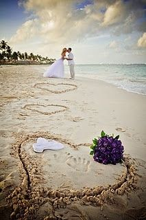 <3 Nice composition with hearts and bridal bouquet on the beach with a kiss of the wedding couple...