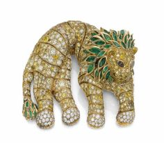 A Colored Diamond, Diamond and Emerald Lion Shoulder Brooch, by René Boivin - Designed as a resting lion, the articulated body pavé-set with diamonds and coloured diamonds, marquise-shaped emerald collet mane and tail end, accented by marquise-shaped brown diamond eyes, 6.9 cm, with French assay marks for gold Signed René Boivin, Paris - Estimate: $156,577 - $260,962