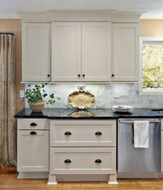 taupe kitchen cabinets; marble tops & backsplash; stainless steel
