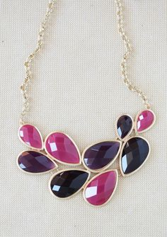 This gold colored necklace features linked raspberry and plum teardrop pendants, creating a gorgeous statement piece.