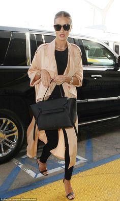 Jetsetter: Rosie Huntington-Whiteley looked extremely chic in a Stella McCartney silk #trench coat and #Frame denim as she glided through LAX airport on April 27, 2016, ready for a flight