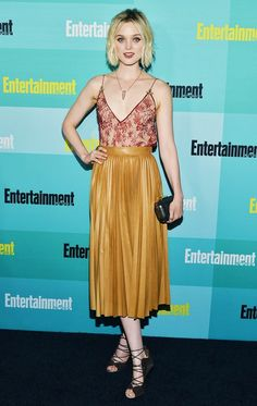 Bella Heathcote wears a lacy black tank, with a mustard pleated skirt, and strappy heels