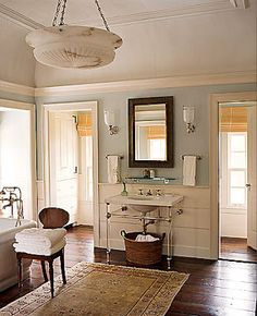 Huge bathroom with great mixes of soft blues, whites and brown wood.  The old floors are awesome.