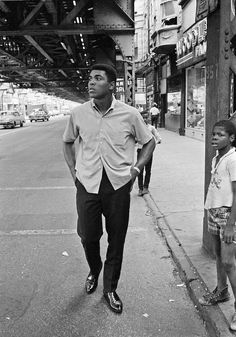 "Muhammad Ali walking under the ""L"" tracks in Chicago's South Side, 1966 © Muhammad Ali, photographed by Thomas Hoepker, 1966"