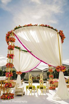 What do you think about using milky white drapes with pretty bunches of flowers for a mandap decor at an outdoor wedding? We think the mandap couldn't have looked more stunning! Also, don't miss to notice the gorgeous pair of chairs for the couple! Wedding Mandap, Desi Wedding, Wedding Events, Wedding Ceremony, Marathi Wedding, Purple Wedding, Gold Wedding, Floral Wedding, Marriage Decoration