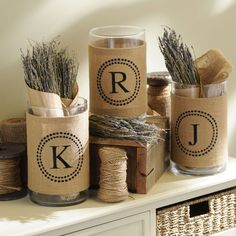 Burlap Monogram Vase at Kirklands.I'm thinking you could make this yourself.wide burlap ribbon that is finished on the sides.and stamp on whatever design you want, then glue around vase. (not that I am that crafty, but it sounds doable.
