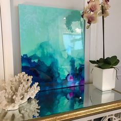 One of a kind abstract artwork is a mixture of acrylics and inks with a resin coating to create a truly unique and serene abstract original. The painting has a glass coat layer of epoxy resin to add a thick high gloss sheen to piece. Looks beautiful in natural light!!  The colors include shades of gold, white, blue, gree, aqua, lilac, iridescent glitter, and touches of real gold leaf.  This is a signed original gallery wrapped heavy duty canvas that is 1.5 deep and 24 wide x 20 high  This…