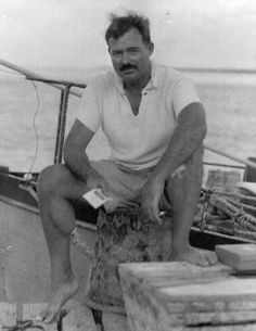 Ernest Hemingway sitting on dock next to his boat, Pilar, circa 1930s.