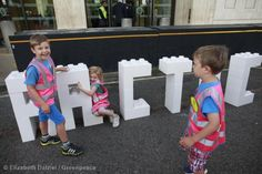 Children with a LEGO blocks spelling Arctic, outside Shell's HQ in London