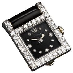 This striking Cartier watch clip epitomizes the Art Deco style. Sophisticated and chic, this fashionable timepiece features a dial and clip of onyx, while sparkling round-cut diamonds comprise the bezel and mark the hours. Crafted of platinum and 18K yellow gold, circa 1920
