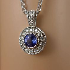 Vintage 14K white gold sapphire and diamond halo pendant on a 14K white gold rolo chain. This lovely necklace features a beautiful sparkling blue sapphire that is surrounded by a halo of diamonds. It has a large bail with diamonds at the top, and is suspended from a beautiful rolo