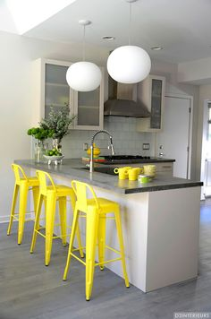 Gray and yellow kitchen features light gray cabinets which pair with concrete…