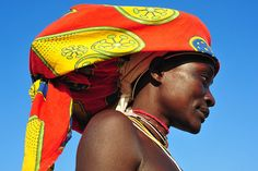 Mucubal fashion, Angola .The headdress is often made of a wicker framework, traditionally filled with a bunch of tied cow tails, decorated with buttons, shells, zippers and beads.