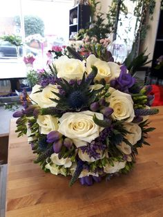 Purple and cream brides bouquet with roses and thistles purple freesia and listen thus wedding day flowers