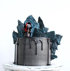 It's a chocolate mud cake + red velvet, layered with chocolate ganache, salted caramel + almond and peanut butter buttercream!  Cake covered in black IMBC, black chocolate drips and black chocolate shards finished with edible black luster dust for basalt-like look and of course cake topper - Kylo Ren figurine made of fondant with isomalt Light saber - ALL edible  Cake inspiration came from my o