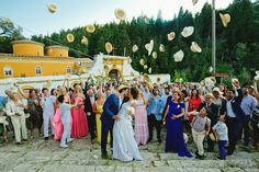 A stylish Greek Wedding in Paxos Island, Greece, where newlyweds kiss and guests throw their hats up in the air celebrating the occasion.