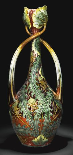 Italian, Cantagalli, circa 1900-1910 VASE of slender ovoid form with twisted lotus leaf handles, the garlic mouth enclosed by the moulded leaf terminals, boldly painted with lush green foliage against a ground of copper lustre whorls and scrolls, cockerel mark and number 10 in black faience, , 21 1/2 in. high