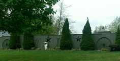 This side yard fence is creatively dressed up with old tools between the evergreens that provide form all year round.
