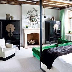The details in this bedroom, black wardrobes, gorgeous green velvet chaise and curtains and wood beams on the ceilings, four poster bed and to top it all up a fireplace!