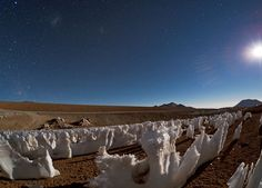 """Babak Tafreshi, one of the ESO Photo Ambassadors, has captured a curious phenomenon on the Chajnantor plateau, the site of the Atacama Large Millimeter/submillimeter array (ALMA). These bizarre ice and snow formations are known as penitentes (Spanish for """"penitents""""). They are illuminated by the light of the Moon, which is visible on the right on the photograph. On the left, higher in the sky, the Large and Small Magellanic Clouds can be faintly seen. Credit: ESO/B. Tafreshi (twanight.org)"""