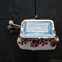「赤花のポーチ」  深い赤い糸と紅茶染めの優しいベージュリネンでアンティーク調に仕上げました。 脇に刺繍糸で編んだ玉を3つ。 もちろん表裏の両面に手刺繍しています。  表布は紅茶染めのリネン。淡いベージュです。(麻100%)  四角いガマ口金具の色はゴールド。 裏地は水色のベルベット地です。  幅約10cm(ガマ口金部分の幅は7.5cm)・高さ7cm  ---------------------------------------------------------------------------- 作品はデザインから刺繍、仕上げまでのすべての工程をひとりで、時間をかけて手作業で行っています。そのため、同じものはお作りできません。全て一点ものです。 (只今オーダー受注は承っておりません。また、海外郵送も承っておりません。)  小さな作品ですが貴方の日々に彩を添えることができますように。