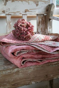 Mom's vintage blankets and pink quilts on rustic wooden bench for the sunporch.