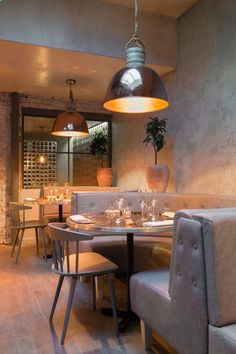 Half-circle bench seating has been used along the walls in the main dining area of this restaurant in London.