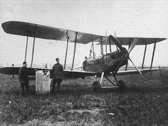 """Lieut. William Leefe Robinson (VC) seated in the BE2c 2963 in which he destroyed Zeppelin """"SL11"""" over NW London 2nd September 1916  The mechanics hold up the upper wing centre section damaged by his own gun during the attack on SL11"""