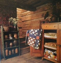 Prim Cupboard...filled with old quilts & crocks in a chippy stand.