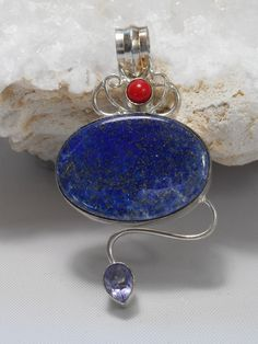 "Gemstone pendant featuring Lapis Lazuli cabachon stone, adorned with cabachon Amethyst and red coral accent stone, bezel-set in 925-sterling silver. Length: 2.2"" including bail. Width: 1.2"""